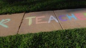 `We love our teachers` written with sidewalk chalk