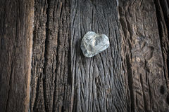 Love out of a rock. Love sign rock. Sitting on a wooden table made out of old barn wood Royalty Free Stock Photography