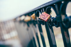 A love padlock attached to a black, metal fence Royalty Free Stock Image