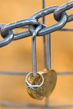 Love padlock and engagement ring hanging from a chain Royalty Free Stock Photography