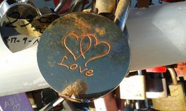 Love padlock. Round metal padlock engraved with love and two inter-twined hearts Royalty Free Stock Photo