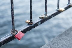 Love Padlocks on a bridge in Stockholm. Varios Love Padlocks on a bridge in Stockholm showing the Water and Iron Bars Royalty Free Stock Photo