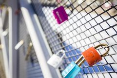 Love locks hanging on a from white metal footbridge, Helsinki, Finland. Red / orange lock with heart in the foreground. Shallow de. Love padlocks closed on stock photos