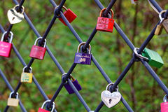 Love padlocks at fence. Different-colored padlocks hanging on a fence outside in a park in Germany. Signs of love and devotion Royalty Free Stock Photography