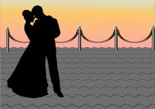 The in love pair on a pier. The couple stands on a pier during a sunset Stock Photos