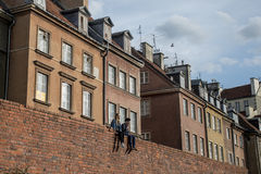Love pair sitting on wall in Warsaw Poand and look daydreaming in front of houses Stock Image
