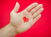 Love in the palm. Love in a man's hands with lots of feelings and emotions from a relationship suggested by a heart drawn on a palm over a red background Stock Photos