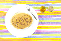 Love Pancake with sweet honey and sugar palm in glass shot. On colorful background Stock Images