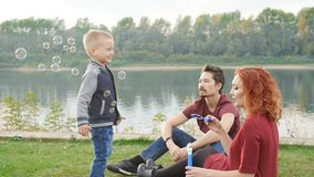Love and parenthood concept. Happy Family with children blow soap bubbles outdoors. Love and parenthood concept. Happy young Family with children blow soap stock footage