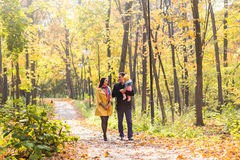 Love, parenthood, family, season and people concept - smiling couple with baby in autumn park Stock Images
