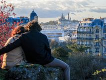 In love in Paris. Couple hugging in Parc des Buttes Chaumont, Paris overlooking the city with the Sacre Coeur in the background royalty free stock images