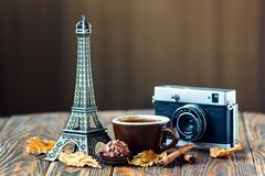 Love Paris! Rose, vintage camera, Eiffel tower, coffee cup, chocolate and cinnamon sticks on wooden background. St Valentine`s Day