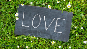 Love in a park. Love written on a board with chalk in a park stock image