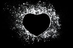 Love, passion, care concept. Freeze motion of white powder  on black dark background. Abstract design of dust cloud. Particles heart shaped explosion screensaver Royalty Free Stock Images