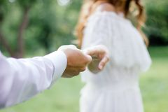 Love and passion concept - young woman and men holding hands of each other. Royalty Free Stock Photo