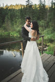 Love and passion - kiss of married young wedding couple near lake.  Royalty Free Stock Photo