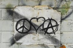 Love Peace and Anarchy. Love, peace, and anarchy grafitti tagged on a weathered and worn urban building. This political statement illustrates unrest and royalty free stock images