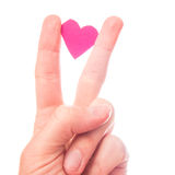 Love and peace. Small pink paper heart squeezed between two fingers doing the peace and victory symbol. To be used in love or peace concepts - focus is best on royalty free stock images