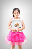 Love pet concept.little girl holding a picture of her dog. Love pet concept.little girl standing and holding a picture of her dog.isolated on grey background Stock Images