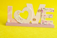 Love in pink letters  on a yellow background Royalty Free Stock Image