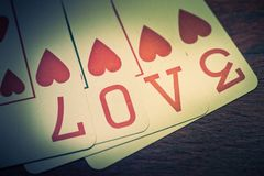 Love, poker playing cards with heart symbol that form the written love. On a wooden shelf. Idea for greeting card for Valentine`s Day or other occasion royalty free stock image