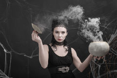 Love potion. Beautiful girl in the image of a witch preparing a magic potion. Carnival costume for Halloween Stock Image