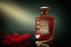 Love potion in a bottle. Red love potion in a bottle with chains and crystal heart around the bottle royalty free stock photos