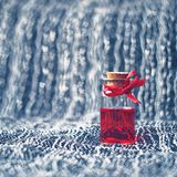Love potion. Little bottle with red ribbon and heart background Royalty Free Stock Images