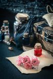 Love potion, red drink in bottle. Magic concept. Love potion. Magic concept wit red liquid in small bottle, wooden box, old paper and flowers royalty free stock photography