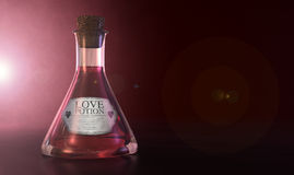 Love Potion. A regular old goblet glass bottle filled with a pink liquid with a label showing it is love potion and sealed with a cork on a spotlit pink Stock Image