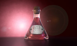 Love Potion. A regular old goblet glass bottle filled with a pink liquid with a label showing it is love potion and sealed with a cork on a spotlit pink Stock Photography