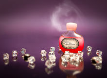 Love potion in small bottle. Red love potion in small bottle with heart shaped smoke above the bottle royalty free stock photography