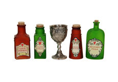 Love potions. Silver antique chalice with grapes and leaves embossed on the sides and bright colorful love potions Stock Image