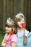 Love Princesses. Two gorgeous caucasian little girls with princess tiara and red love heart sticks, looking dreamy Royalty Free Stock Photos
