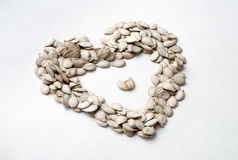 Love pumpkin seeds isolated heart shaped Stock Photo