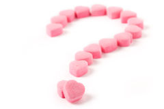 Love Puzzle. Pink Heart Shape Candy and Question Mark, Love Puzzle Stock Photo
