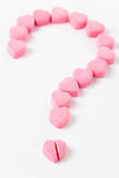 Love Puzzle. Pink Heart Shape Candy and Question Mark, Love Puzzle Royalty Free Stock Photo
