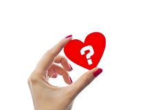 Love is a question. Woman hand is holding red heart shape with question mark inside of it isolated on white royalty free stock photos