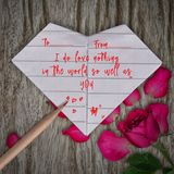 Love Quotes in Origami paper white heart, pencil and rose pink f. Lower on wooden table background stock photo