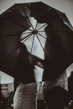 Love in the rain / Silhouette of kissing couple under umbrella stock photo