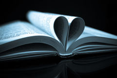 Love reading. Pages of a book curved into a heart shape Stock Photos