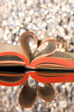 Love reading. Open book with pages in the form of a heart with bokeh background Stock Image