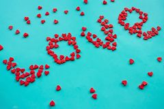 Love, red hearts. The inscription love is made of little red hearts. An explanation in love, strong feelings. Bright blue background, daylight royalty free stock image