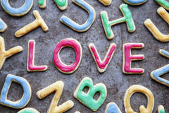 Love in red icing amongst letter shaped cookies, close-up Stock Photo