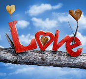 Love. Red love letters stuck in a tree branch. The tree has heart shaped leaves. The sky is a pretty blue with soft clouds. Valentines day concept royalty free stock photos