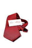 Love always red necktie gift. Red tie with a white gift tag that reads love always in red, isolated on a white background Royalty Free Stock Photography