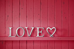 Love Red Valentine Background. A red painted wood background with the word love and a heart Stock Photo