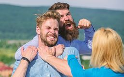 Love relations issue. Man aggressive attacks lover of his girlfriend. Leadership and competition concept. Woman tries to. Stop violence, two men fighting stock images