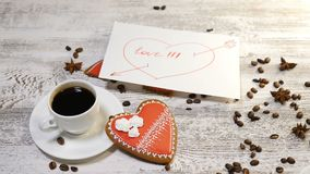 Love relations. St. Valentine concept. Top view of cup of coffee and a ginger biscuit heart shaped are on wooden. Background with coffee beans around. Female stock video footage