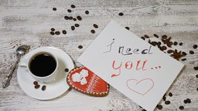 Love relations. St. Valentine concept. Top view of cup of coffee and a ginger biscuit heart shaped are on wooden. Background with coffee beans around. hand puts stock video